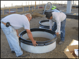 MwayPro Watertight Manhole Cover- two men placing parts on base